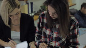 Two young women in the office look at some documents and talking, a man sitting behind them. One girl has dark hair and is dressed in a plaid casual shirt, the stock video footage