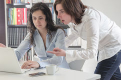 Two young women in office working together on desktop. Stock Images