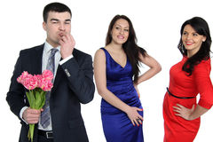 Two young women and one gay. A men with a bouquet of flowers and two young women Royalty Free Stock Image