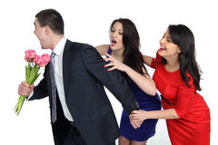 Two young women and one gay. A men with a bouquet of flowers and two young women Royalty Free Stock Photos