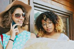 Two young women, one on phone. Two pretty young women one wearing a large floppy hat, spectacles and using her mobile , the other African American  standing Royalty Free Stock Photography