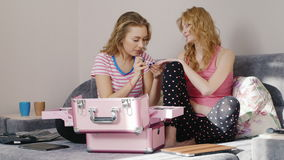 Two young women paint the nails at home. They sit in their pajamas on the bed. HD video stock footage