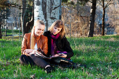 Two young women in the park. Two young women reading magazine in the park Stock Photography