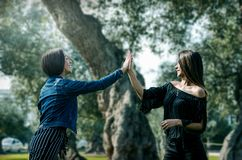Two young women on the park giving high five. royalty free stock photos