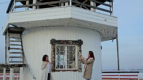 Two young women are photographed on the background of the lighthouse. stock video