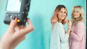 Two young women are photographed in a photo studio: backstage. Professional photosession: two girls model posing on a turquoise, camera screen. Two young women stock video