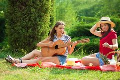 Two young women on a picnic playing a guitar and having fun Stock Image