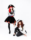 Two young women in pirate costumes on white background Stock Photos