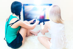 Two young women playing. In computer games. Bright white colors Royalty Free Stock Images