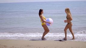 Two young women playing with a beach ball. Two young women in bikinis playing with a beach ball on a sandy tropical beach in the summer sunshine  side view stock video