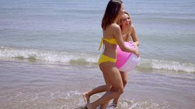 Two young women playing with a beach ball. Two young women in bikinis playing with a beach ball on a sandy tropical beach in the summer sunshine  side view stock footage