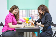 Two young women playing chess Royalty Free Stock Photography