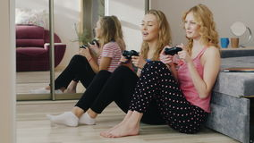 Two young women playing on the console. Sit on the floor near a mole. Have fun together, girlfriends pajama party. HD video stock video