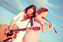 Two young women playing guitar Stock Photos