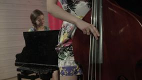 Two young women playing a musical instruments. Two girls playing a musical instruments stock video
