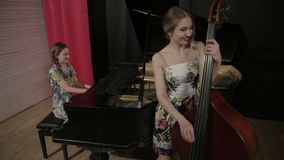 Two young women playing a musical instruments. Two girls playing a musical instruments stock video footage