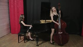 Two young women playing a musical instruments stock video