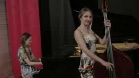 Two young women playing a musical instruments stock video footage