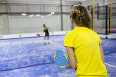 Two young women playing paddle tennis. Royalty Free Stock Image