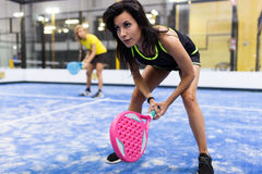 Two young women playing paddle tennis. Stock Photos