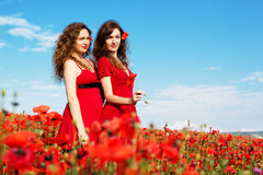 Two young women playing in poppies field Stock Images