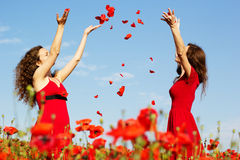 Two young women playing in poppies field Stock Image