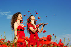 Two young women playing in poppies field Royalty Free Stock Photos