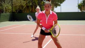 Two young women playing tennis doubles stock video footage