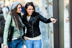 Two young women pointing at a show-window Stock Photography