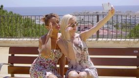 Two young women posing for a selfie outdoors. Two stylish trendy young women posing for a selfie outdoors standing close together on an outdoor patio overlooking stock video footage
