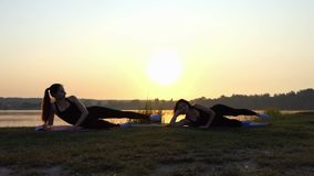 Two Young Women Practice Yoga Lying on Mats on a Lake Bank at Sunset. Two Sportive Young Women Raise Their Left Legs While Lying on Their Mats on a Picturesque stock video footage