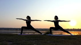 Two Young Women Practice Yoga on The Picturesque Lake Bank at Sunset. Two Beautiful Young Women Practice a Warrior Yoga Exercise With a Long Lunge on the stock video footage