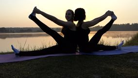 Two Young Women Practice Yoga Sitting on Mats Back-To-Back at Sunset in Slo-Mo. Two Young Women Sit on Mats Back-To-Back, Touch One Foot With Their Fingers stock footage
