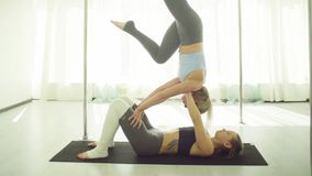 Two young women practicing acrobatic yoga. Two young women practicing acrobatic yoga in studio stock video footage