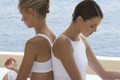 Two young women practicing yoga Stock Photography