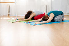 Two young women practicing yoga asana on floor in gym Royalty Free Stock Images