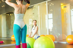 Two young women Prepare for training gymnastics. Class with fit balls. beautiful sports shape fit figure back girls in light modern club Stock Images