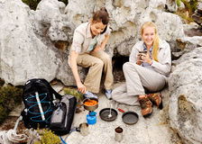 Two young women prepares something to eat. Two friendly women cook up some food while camping in the wilderness. outdoor hiking lifestyle concept royalty free stock photography