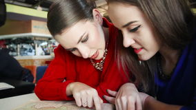 Two young women reading a book in a cafe. Two girls read the book in a cafe and discuss plans stock footage