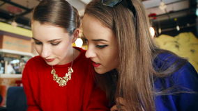 Two young women reading news in a cafe. Two girls read in a cafe and discuss plans stock video footage