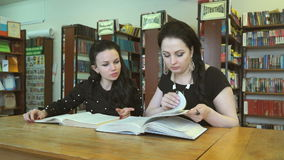 Two young women reading textbooks at library stock video footage