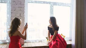 Two young women in red cocktail dress posing and photograps at smartphone on window stock footage