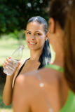 Two young women relaxing after fitness in park Stock Image