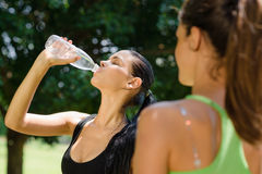 Two young women relaxing after fitness in park Stock Photo