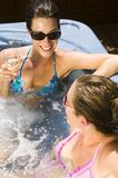 Two young women relaxing in a Jacuzzi Stock Photo