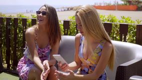 Two young women relaxing at an outdoor cafe. Two young women relaxing on a couch at an outdoor cafe checking for messages on a mobile phone with focus to a stock video footage
