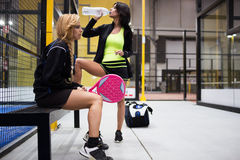 Two young women relaxing after the paddle tennis match. Stock Images