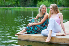 Two young women relaxing. In the park near the pond Royalty Free Stock Image