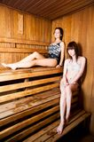 Two young women relaxing in a sauna Royalty Free Stock Photo