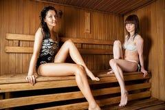 Two young women relaxing in a sauna Stock Photos